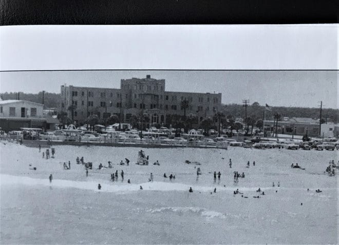 Flagler Beach is shown with summer visitors in July 1964. The large building is the Flagler Beach Hotel, which fronted on Veterans Park. The hotel was built by Dana Fellows Fuquay and George Moody, and had its grand opening on July 4, 1925. It was torn down in 1972.