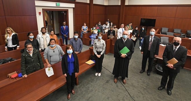 Hailing from 10 countries, 17 new U.S. citizens are shown, Oct. 23, 2020, following a citizenship and naturalization ceremony at U.S. District Court in Erie. Presiding over the ceremony (shown at center) is U.S. Bankruptcy Judge Thomas P. Agresti. To the right of Agresti is Erie Mayor Joe Schember. To the far right is Assistant U.S. Attorney Christian Trabold. New citizens include: Nicholas Omokefe Eroraveno, Indira Kafley, Radka Gregush, Goma Maya Adhikari, Phyu Phyu Win, Colleta Nyamungo Maniraguhu, Michael Anubondem Awungnkeng, Amal Ali Salman, Socorro Loya Huffman, Purna Maya Gurung, Mahsa Shateri, Dendup Tamang, Griselda Arevalo Villa, Matthew Ivor Alexander, Samy Dieumerci Kiss Bolonda, Suka Bahadur Tamang and Jeera Maya Majhi.