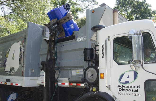 A mechanical arm dumps a 95-gallon recycling container into an Advanced Disposal truck in this 2015 photo.