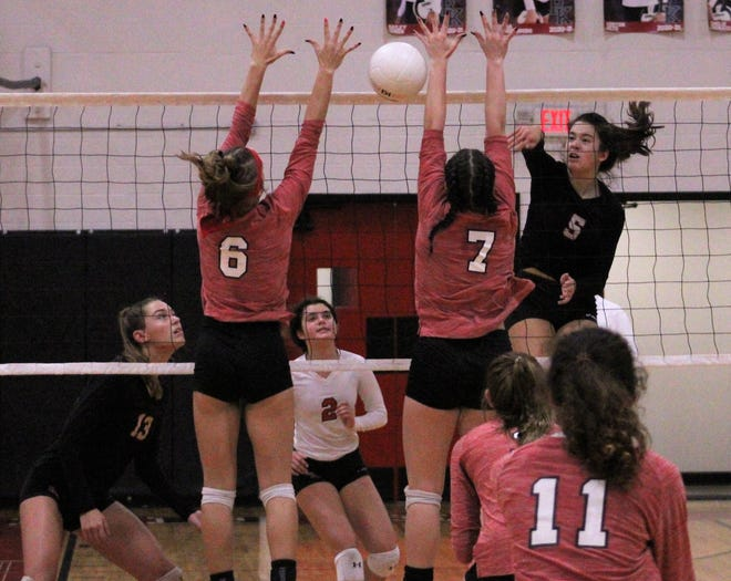 Bishop Kenny's Bailey Chin (5) spikes the ball as Baker County's Allyson Crossland (6) and Chloe Clevenger (7) attempt to block during the FHSAA Region 1-4A volleyball quarterfinal on Thursday night.
