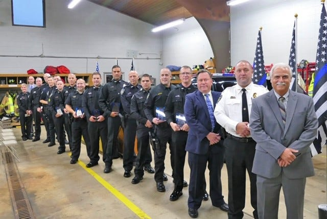 Perry Township trustees honored police officers for their service. Members of the force for 10 or more years were given a plaque.