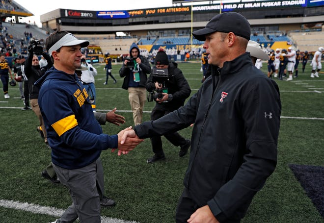 West Virginia coach Neal Brown, left, and Texas Tech coach Matt Wells shake hands after the Red Raiders' 38-17 victory last year in Morgantown, West Virginia. The two teams meet again Saturday at Jones AT&T Stadium.
