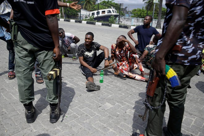 Police officers stop and search a bus carrying passengers around Lekki toll gate in Lagos, Nigeria, on Friday. Resentment lingered with the smell of charred tires Friday as Nigeria's streets were relatively calm after days of protests over police abuses, while authorities gave little acknowledgement to reports of the military killing at least 12 peaceful demonstrators earlier this week.