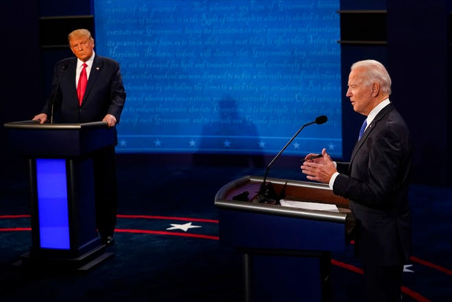 Democratic presidential candidate former Vice President Joe Biden answers a question as President Donald Trump listens during the second and final presidential debate Thursday, Oct. 22, 2020, at Belmont University in Nashville, Tenn.