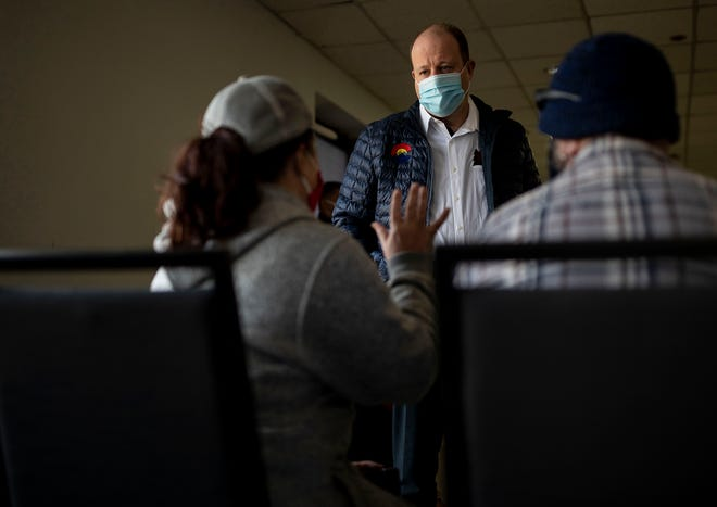 Colorado Gov. Jared Polis speaks with Grand Lake residents CarrieAnn Mathis and her husband Walter Mathis during a visit with evacuees of the East Troublesome fire at The Vintage Hotel in Winter Park, Colo., on Friday. The East Troublesome fire exploded into the second largest wildfire in the state's recorded history, causing thousands of residents to evacuate.