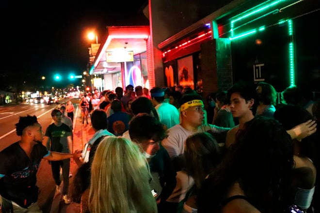 In this photo provided by Fresh Take Florida, people wait in line outside a bar following a University of Florida football game on Sept. 16 in Gainesville. College students across Florida are packing bars off campus and private parties while breaking rules about wearing masks and maintaining social distance during the fall semester — and other students themselves are often reporting violations to authorities.