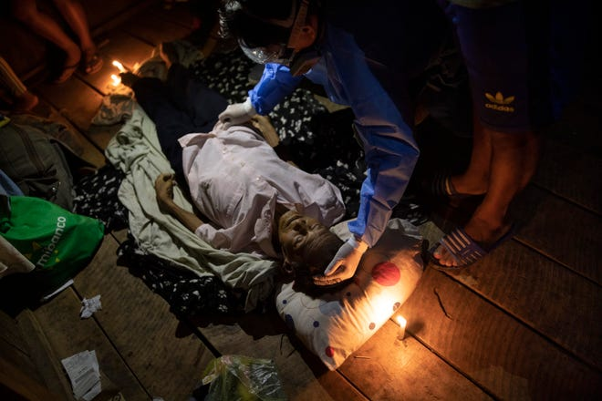 Illuminated with candles and a cellphone's blue light, a doctor examines the lifeless body of Jose Barbaran who is thought to have died recently from complications related to the new coronavirus, in a relative's home in Pucallpa, in Peru's Ucayali region.