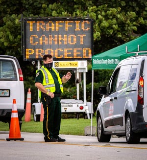 Palm Beach County sheriff's deputies establish a security checkpoint along South Ocean Boulevard just north of Phipps Ocean Park earlier this month before President Trump's visit. He is slated to be back in town on Sunday.