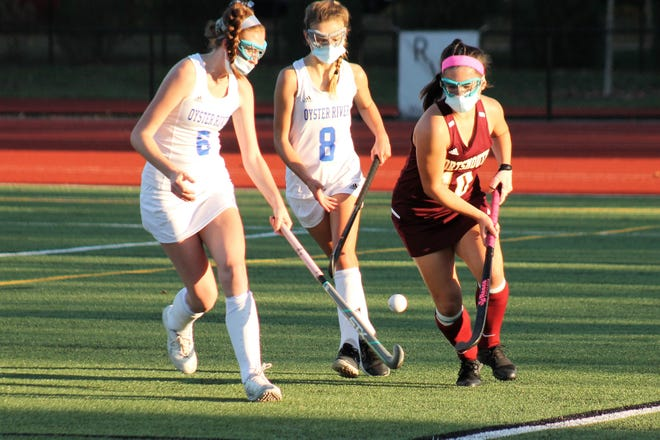 Portsmouth's Mia Edwards, right, tries to beat Oyster River defenders Jenn Newick (6) and Annika Kell (8) along the sideline during Division II playoff action Thursday in Durham.