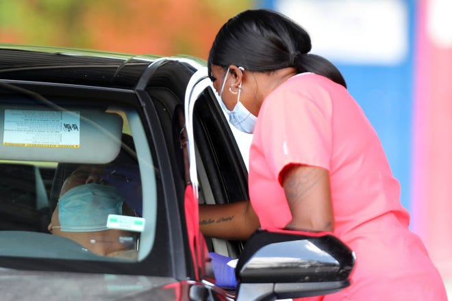 Spector Scientific Lab mobile phlebotomist Shernetta Bryant swabs a man for COVID-19 at a drive-through free testing site in the parking lot of Cheetah Gentleman's Club in Pompano Beach, Florida on Tuesday, Sept. 29, 2020. (Amy Beth Bennett/South Florida Sun Sentinel/TNS)