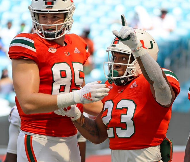 Cam Ron Harris (23) celebrates his first-quarter touchdown with Will Mallory during Miami's victory over Pittsburgh last Saturday at Hard Rock Stadium .