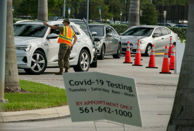 People wait in their cars to be tested Oct. 23 for the coronavirus at a drive-thru rapid testing site at the FITTEAM Ballpark of the Palm Beaches in West Palm Beach.