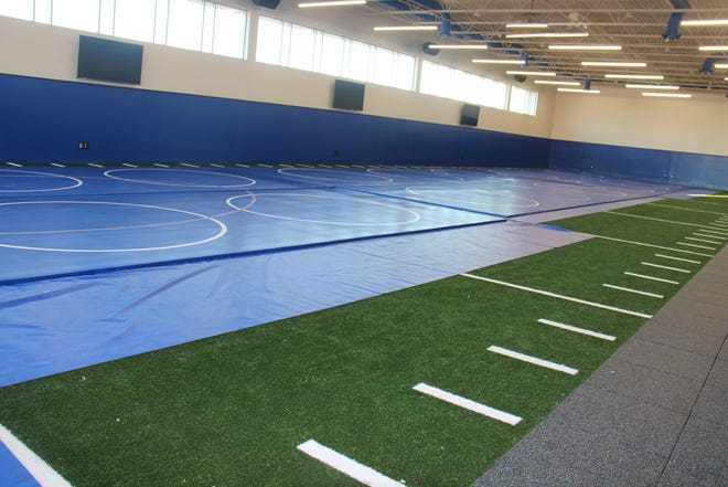 The multipurpose/wrestling addition features turf as well as wrestling mats.