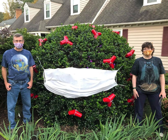 Robert and Wendy Linkous stand in their Chester yard by the holly bush decorated as a coronavirus germ for Halloween on October 22, 2020.