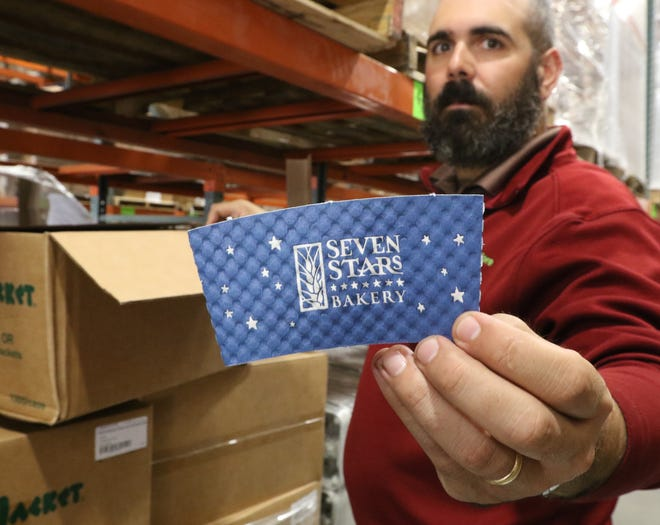 Vincent Fonseca holds a coffee sleeve for Seven Stars Bakery. Packaging and More provides the chain with many other items, including their bread bags and iced coffee cups. [The Providence Journal / Sandor Bodo]