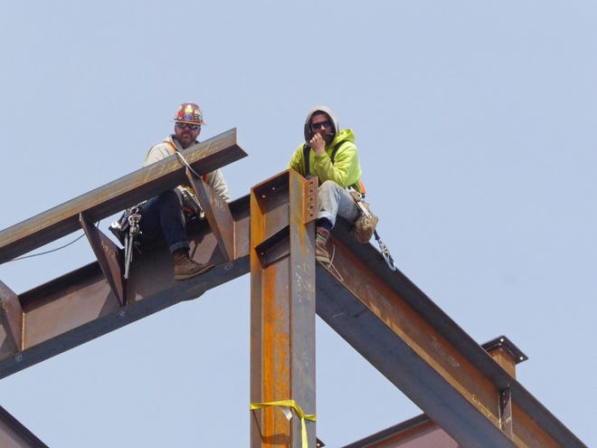 Workers wait for a beam while constructing a building in Providence in 2018. Economists told state budget writers that the Rhode Island economy has improved but the state isn't likely to recover all of the jobs it had before the coronavirus pandemic until 2023 or early 2024. (The Providence Journal file / Sandor Bodo)