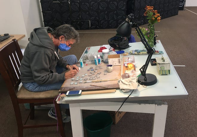New Zone president and ceramic maker Diane Story Cunningham paints a tiny house, one of 50 buttons she will donate to Eugene ShelterCare's fundraiser.