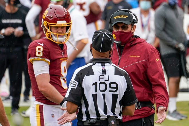 Washington Football Team head coach Ron Rivera and quarterback Kyle Allen talk to field judge Dale Shaw (104) during the first half against the Los Angeles Rams on Oct. 11 in Landover, Md. The first game between 1-5 Washington and the 2-4 Dallas Cowboys since the name change is also the longtime NFC East rivals' first meeting with this bad a combined winning percentage since 2001.