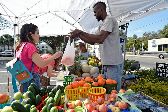 Steven Gilbert, 48, helps out Christina Harn, 21, left, and her friend Sarah Scully, 21, middle, during the Newtown Farmers Market in 2017. The city of Sarasota is revising its Newtown business assistance grant program to help spur more small business owners.