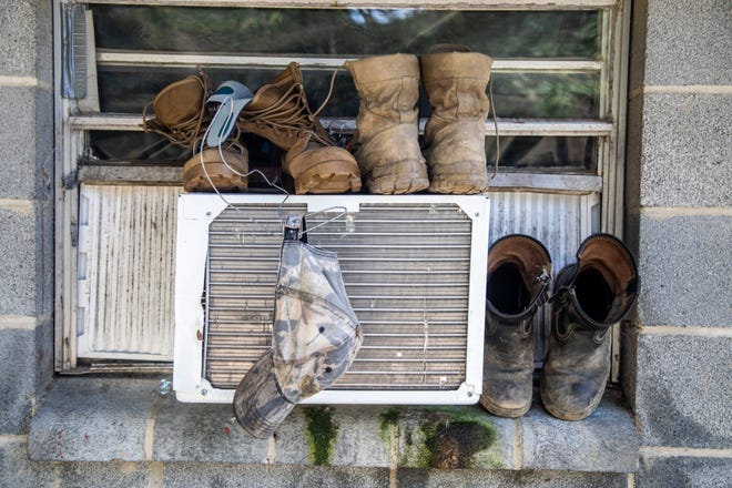 Boots and a hat dry on a window air conditioning unit at a Johnston County farmworker camp Thursday August 27, 2020. Air conditioning is considered a luxury by many farmworkers in North Carolina farmworker camps.