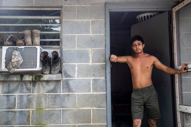 A farmworker named Javier stands in the doorway of his living quarters at a Johnston County farmworker camp Thursday August 27, 2020. Air conditioning is considered a luxury by many farmworkers in North Carolina farmworker camps.