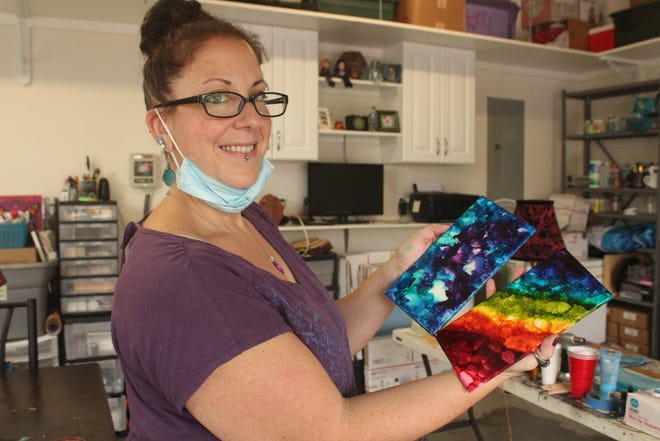 Jenn Maksymiak poses in her studio with two pieces of artwork. Maksymiak shifted her focus to online sales after COVID-19 cancelled many of the festivals where she would typically sell her work.