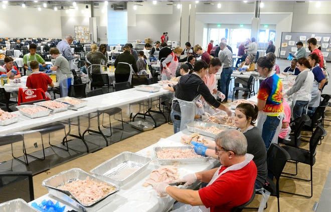 Volunteers shred turkey during preparations for the 2018 CommUnity Thanksgiving Celebration in Gadsden. This year's event is set for Nov. 25, after last year's meal was canceled because of the COVID-19 pandemic.
