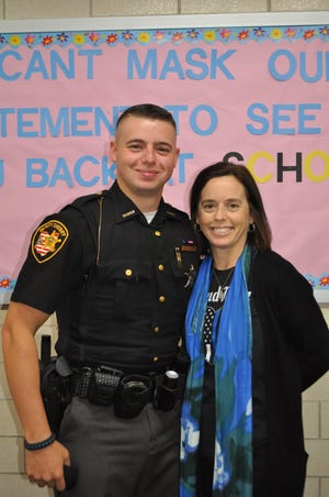 Will Love of the Tuscarawas County Sheriff's Office poses with his mother, Tricia, a teacher at the school.