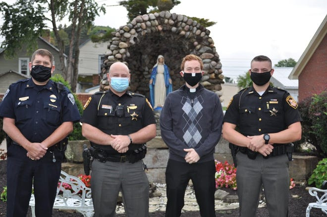 Vince Beal, Uhrichsville Police Department, Travis Stocker, Tuscarawas County Sheriff's Office, Fr. Tom Gardner, and Will Love, Tuscarawas County Sheriff's Office attended the ceremony at Immaculate Conception.