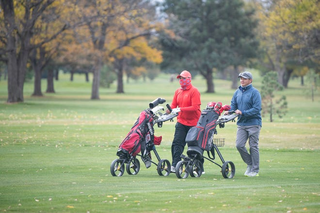 Seth Nunez, left, and Tyler Nunez walk the fairway of the 10th hole at Elmwood Golf Course on Friday October 23, 2020.