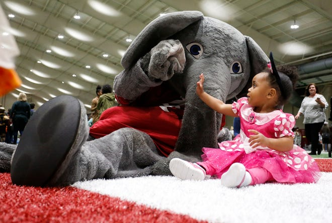 Big Al gives high five to Kayleigh Smith during the Halloween Extravaganza Monday, Oct. 28, 2019 in the Hank Crisp Indoor Practice Facility. [Staff Photo/Gary Cosby Jr.]