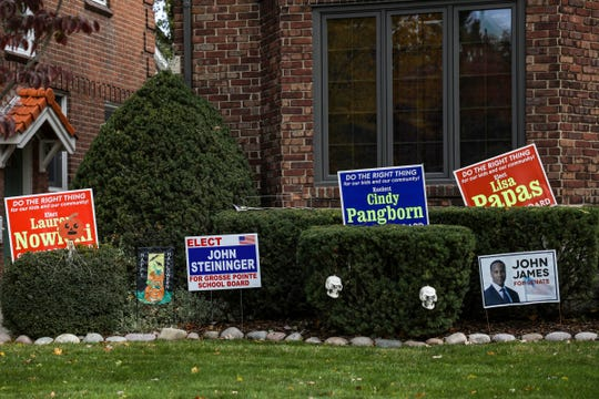Political yard signs for Grosse Pointe School Board candidates Lauren Nowicki, John Steininger, Cindy Pangborn, Lisa Papas, and Republican U.S. Senate Candidate John James in front of homes in Grosse Pointe, Mich. on Oct. 21, 2020.