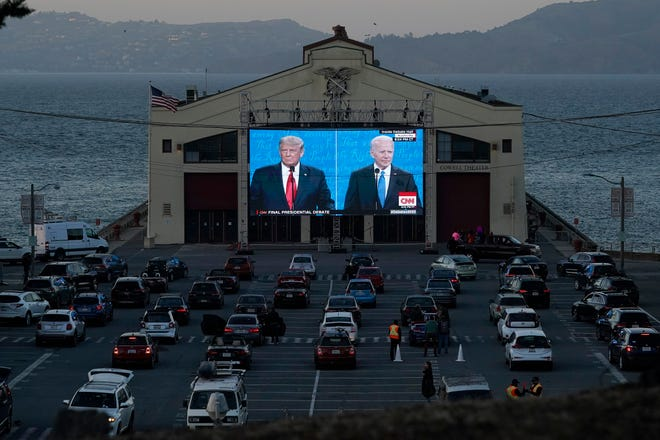 People watch from their vehicles as President Donald Trump, on left of video screen, and Democratic presidential candidate former Vice President Joe Biden speak during a Presidential Debate Watch Party at Fort Mason Center in San Francisco, Thursday, Oct. 22, 2020. The debate party was organized by Manny's, a San Francisco community meeting and learning place.