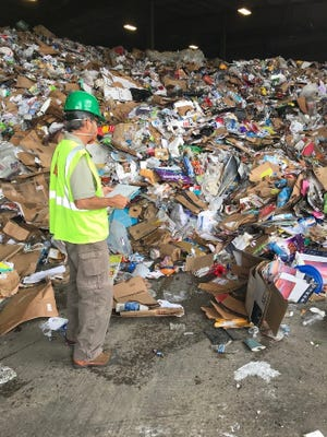 General Manager Mike Csapo inspects a load of recyclables to eliminate contaminated materials.