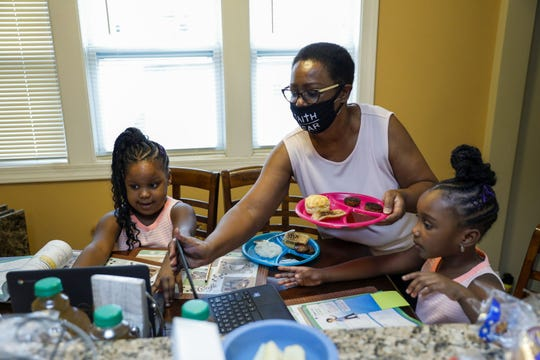 Yvernia Wilson, center, helps gives her 6-year-old twin granddaughters, Faith, left, and Hope breakfast Oct. 15, 2020, before their first grade online learning at their Chicago home. Wilson, 63, has had to figure out how to stretch her grocery dollars. (Jose M. Osorio/Chicago Tribune/TNS)
