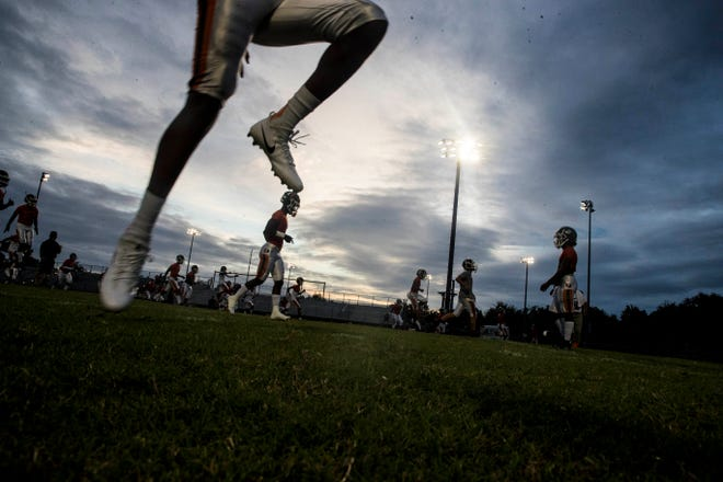 Members of the Dunbar High School football team warm up before a game against Riverdale at Riverdale on Friday.