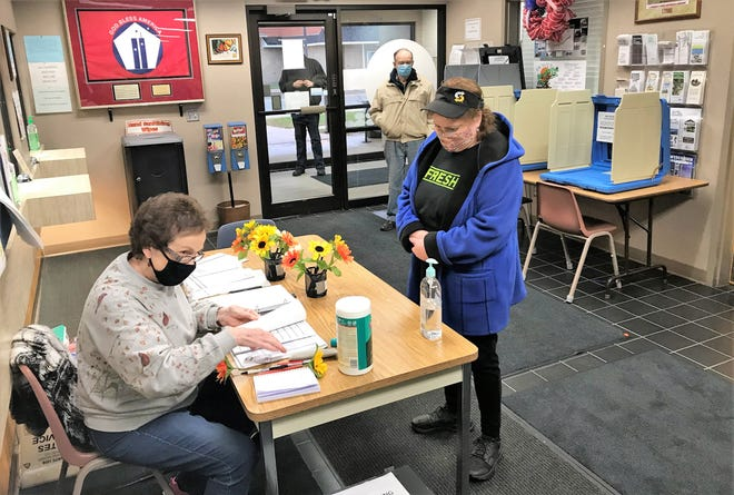 Mary Heiser, an election worker in Oconto, checks the registraiton records for a woman wishing to cast her ballot on Friday, Oct. 23, at Oconto City Hall.