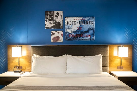 Photographs hang above a bed in a hotel room during the grand opening at Hotel Millwright, Wednesday, Oct. 21, 2020, in Amana, Iowa.