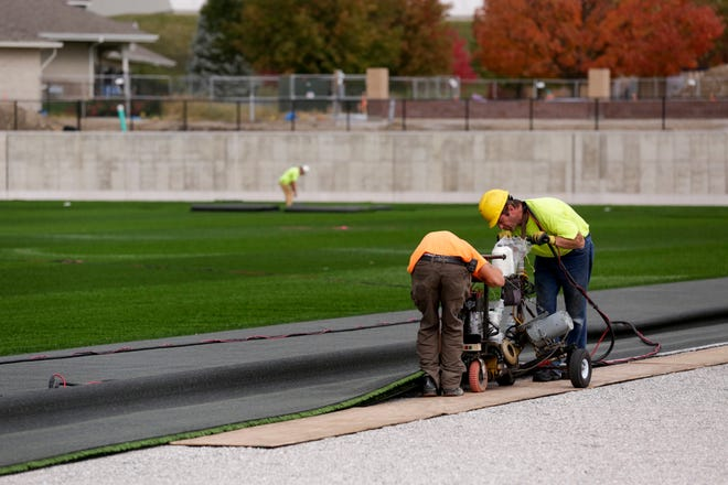 """Workers uses a machine to """"stitch"""" two pieces of artificial turf together in the infield of Loeb Stadium, Friday, Oct. 23, 2020 in Lafayette."""
