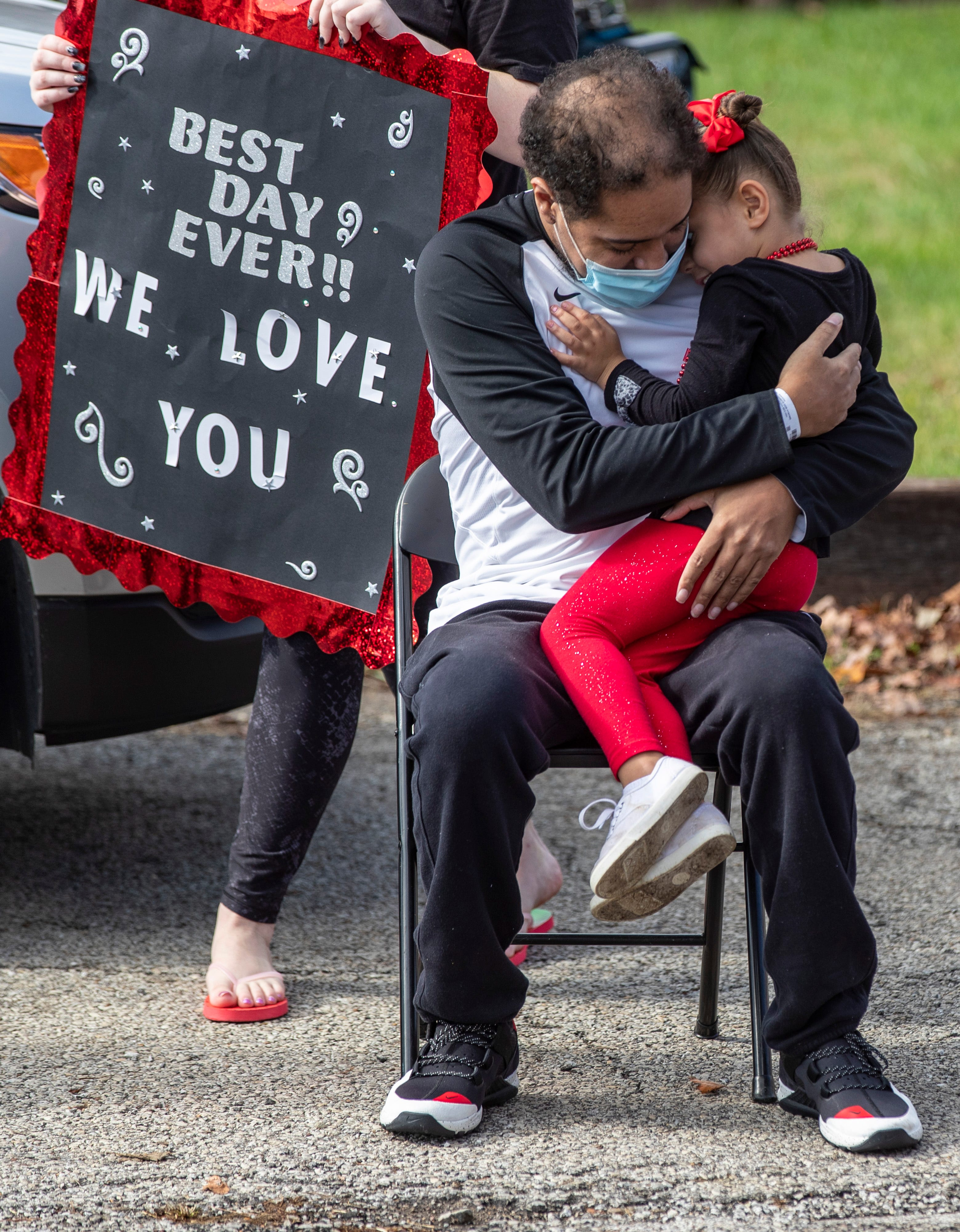 Demetrius Booker, left, embraces his daughter, Mackenzie Booker, 4, after returning home following a 95 day battle with COVID-19 at Louisville Baptist East. Oct. 23, 2020