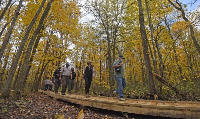 Visitors tour the renovated and upgraded boardwalk that winds around Fowler Woods State Nature Preserve on Friday morning.