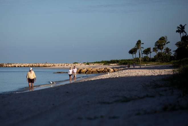 Beachgoers walk along the water near Doctors Pass in Naples on Friday, October 23, 2020. Collier County will begin a beach renourishment project, hauling sand to Naples Beach between Doctors Pass and Lowdermilk Park, in early November.