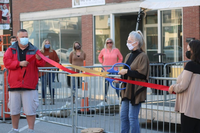 Mary Snyder, of Mary's Blossom Shoppe, who is described as the matriarch of downtown Port Clinton, cuts a ribbon to celebrate the historic district's newly revitalized streetscape.