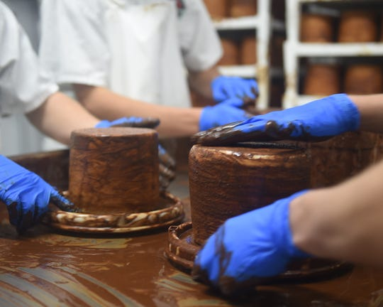 Once the Mad Elf beer cheese wheel is hardened in its mold, workers will apply a coffee and chocolate to the wheel. Workers will finish about 650 wheels per week. Each wheel weighs about four pounds, according to Rynn Caputo of Caputo Brothers Creamery in Spring Grove. The cheese, which is part of a collaboration with Troegs Brewing in Hershey, is finished with the cocoa and coffee rub using Hershey's cocoa and coffee grinds from Little Amp Coffee Roasters, also in Hershey.