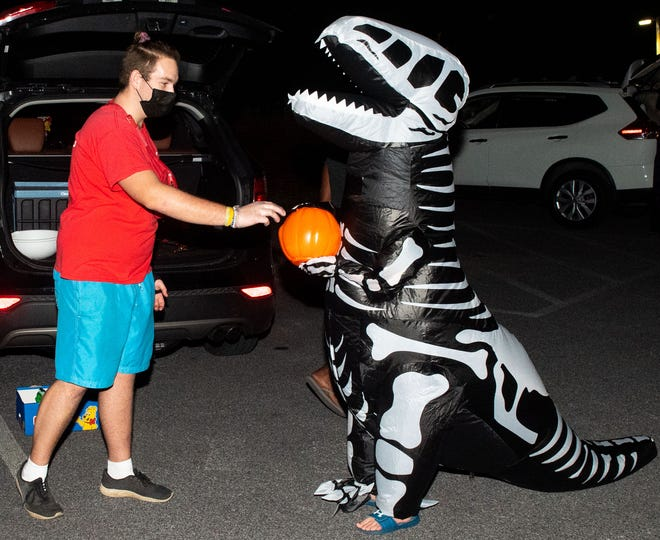 Avery Marcini, 9, is dressed as an undead T-Rex and gets a sweet treat from YMCA Lifeguard Johnathan Baublitz, during the annual Halloween Treat Trail event in the parking lot of the York YMCA held recently.