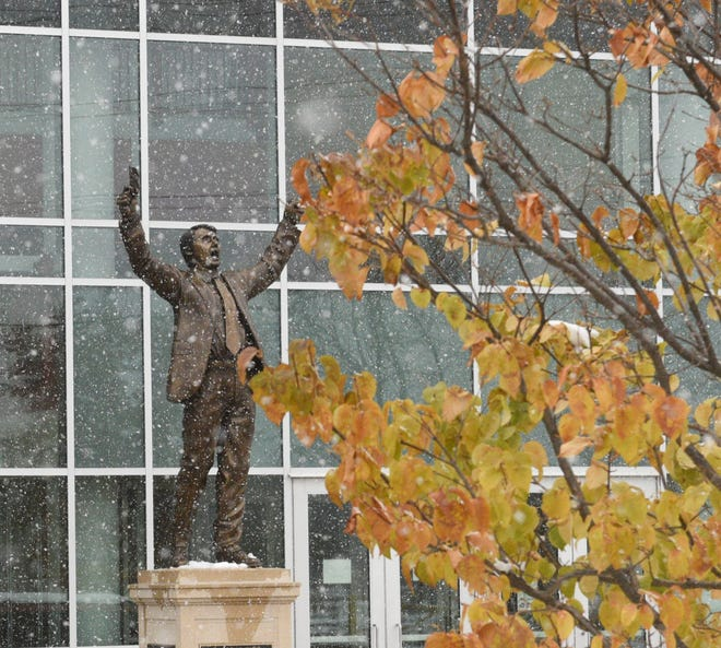 The statue of Herb Brooks stands between scenes of fall and winter Thursday, Oct. 22, 2020, at Herb Brooks National Hockey Center.