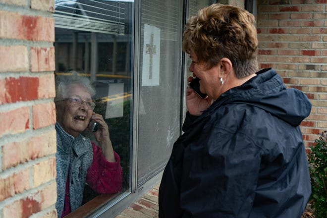 Shirley Sturgill, 91, uses as phone inside her apartment to talk to her daughter, Ann Hankinson, during a window visit at Brookdale Senior Living.