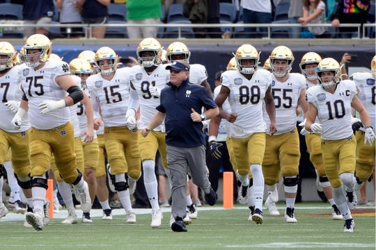 Notre Dame coach Brian Kelly, center, runs onto the field with his players before the Camping World Bowl  against Iowa State in Orlando, Florida.