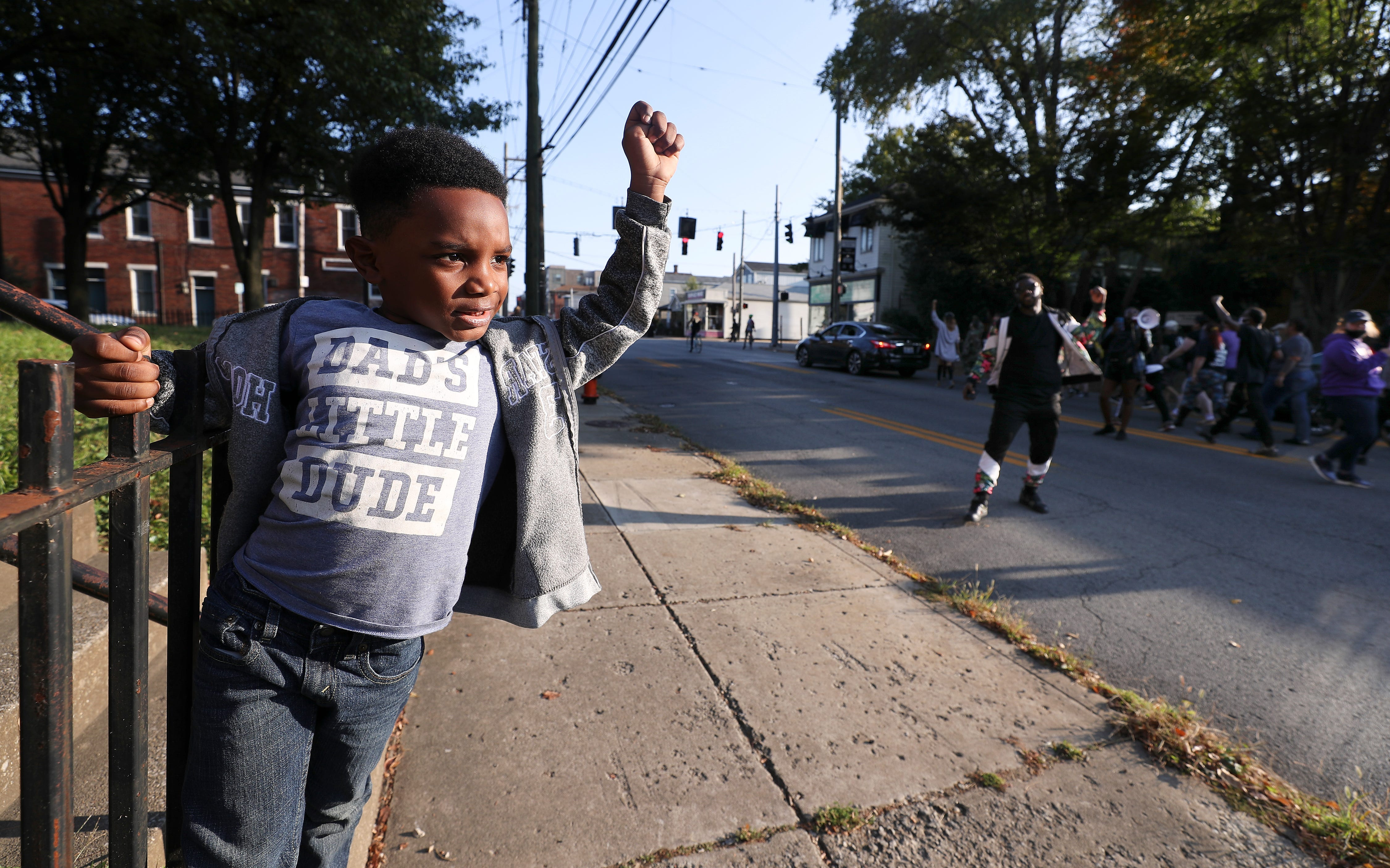 Charles Buntyn, 6, raises a fist in the air in solidarity with passing protesters as they marched down Baxter Ave. during a demonstration to honor Breonna Taylor in Louisville, Ky. on Oct. 6, 2020.