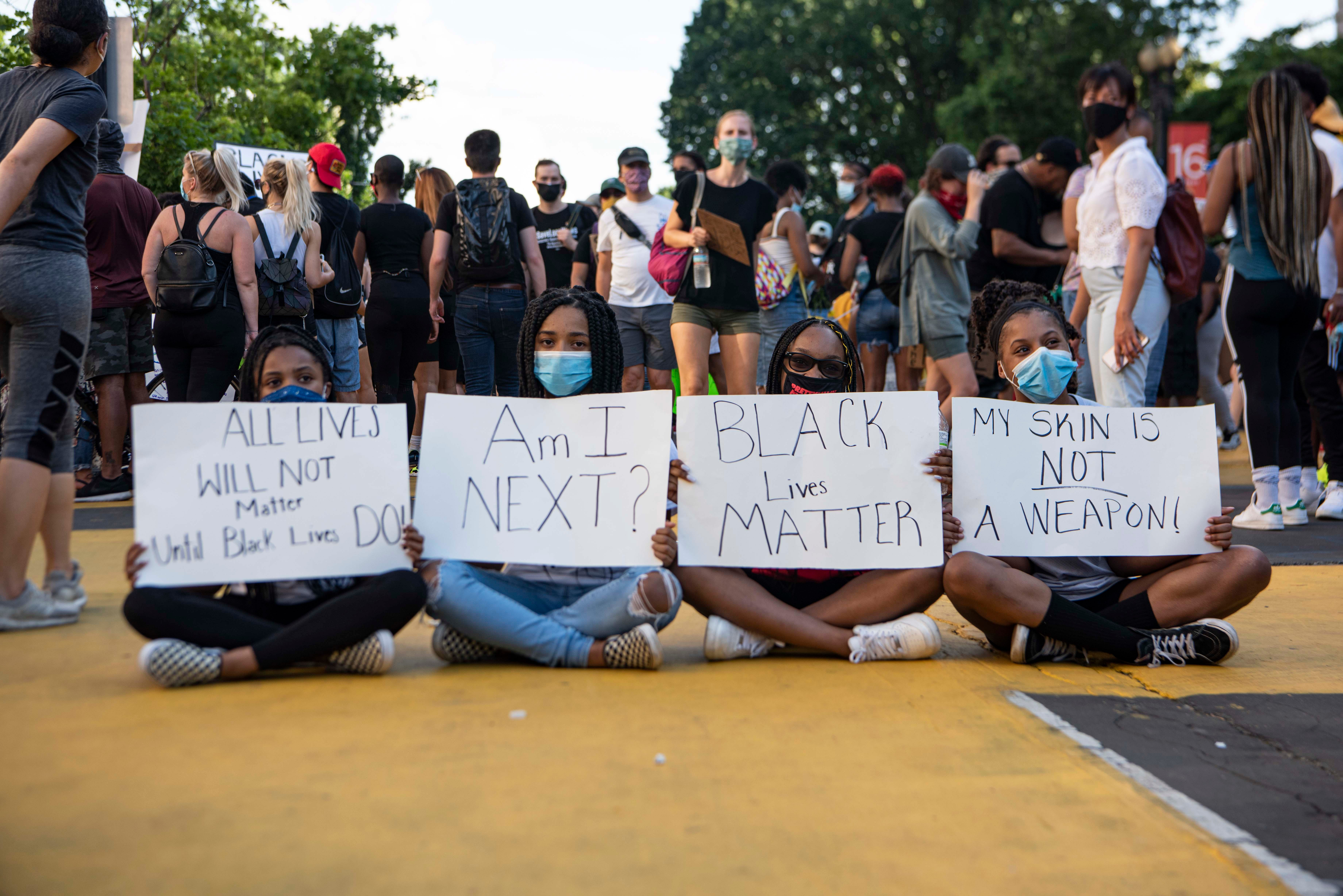 """From left to right, Amari Hawkins, 14, Riley Goins, 15, Kaleigha Kendrick, 14, and Tierra Gibson, 14, hold signs on the newly renamed """"Black Lives Matter Plaza"""" on 16th and I streets in downtown Washington, D.C., on Saturday, June 6, 2020. Protests continued following the death of George Floyd."""